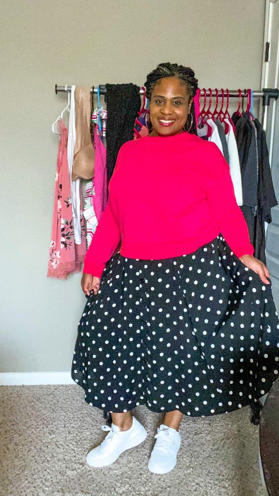 woman wearing plus size black polka dot skirt and pink top
